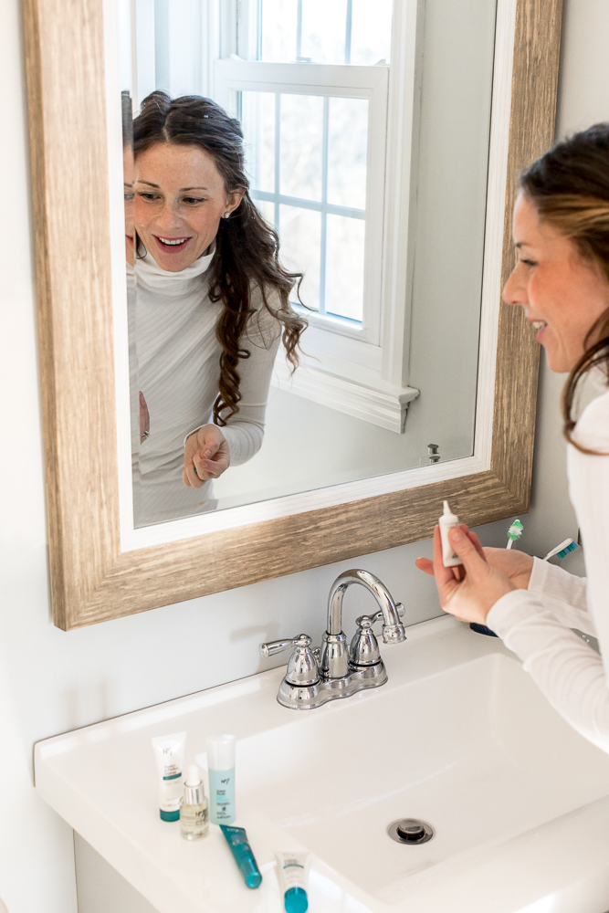 Woman in white turtleneck smiling while holding under eye cream in front of mirror