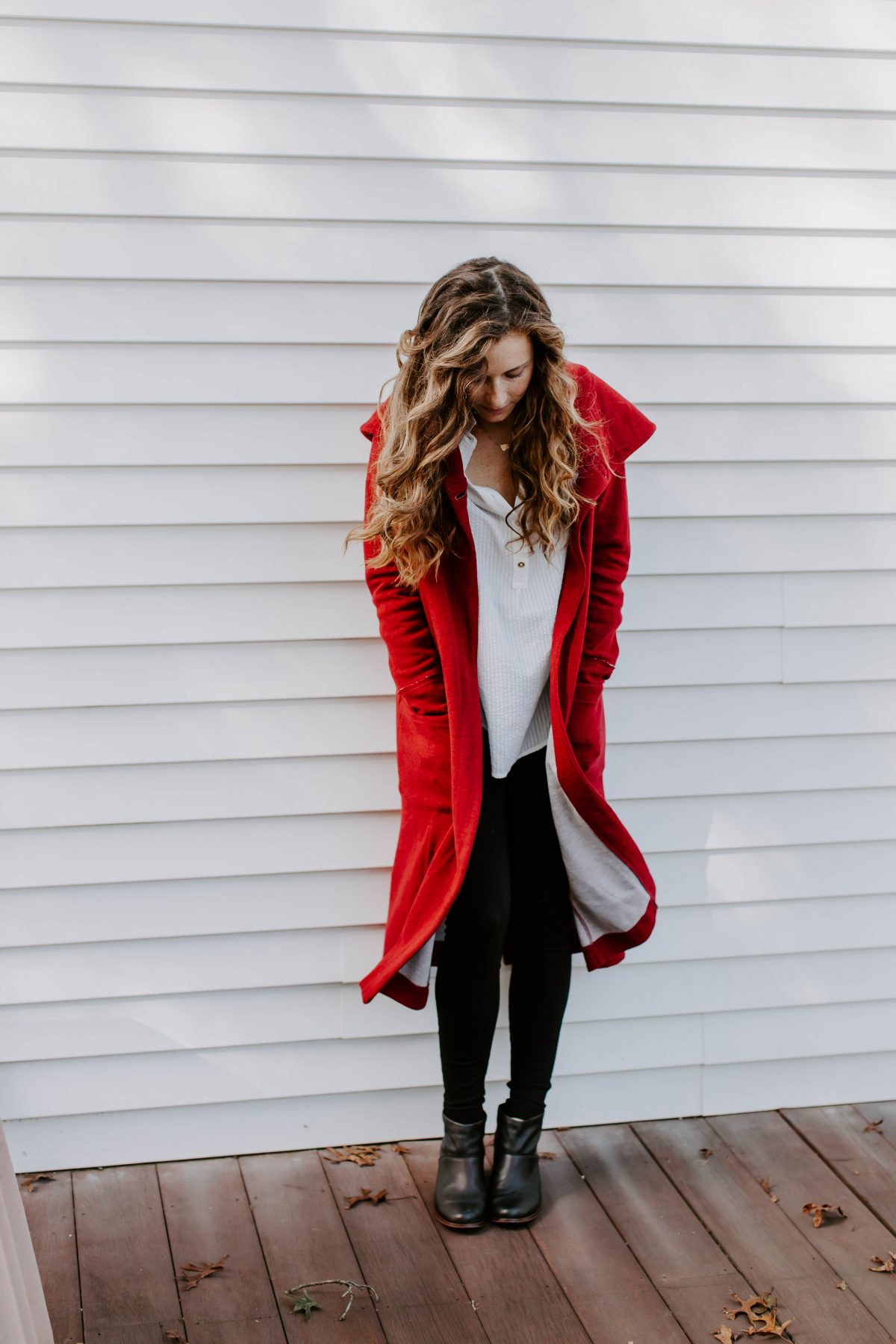 Woman wearing red long coat looking down at her feet