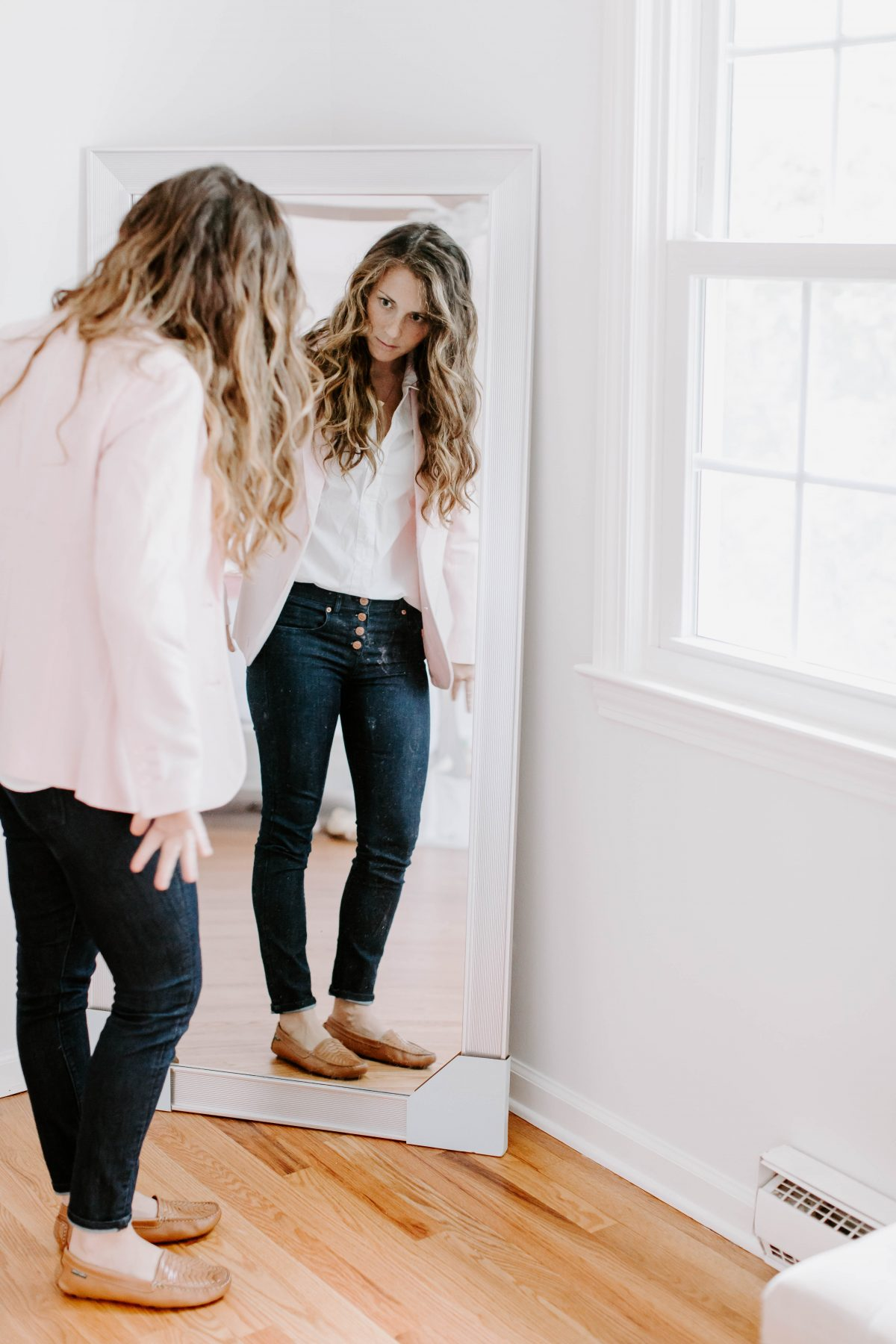Woman looking at herself, pink blazer, white button front shirt, and button front jeans, standing in front of mirror