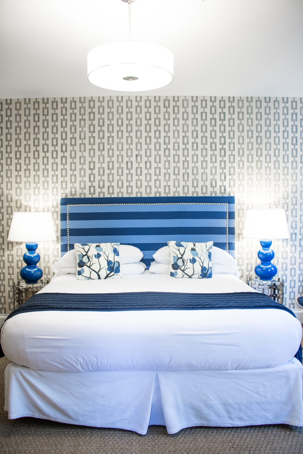 King size bed with blue stripe headboard, white comforter, cable knit blue throw, blue floral pillows, and blue lamps on either side of the bed