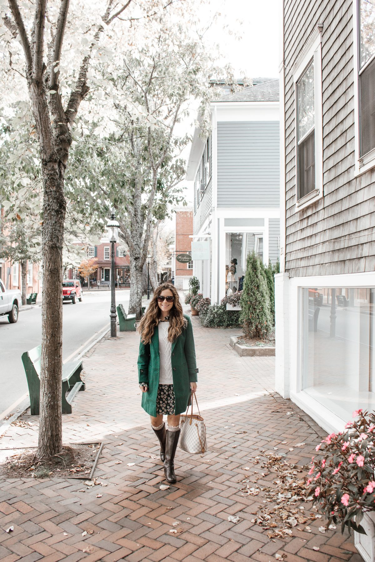 Smiling woman wearing a green peacoat over a sweater and dress on the street in Nantucket