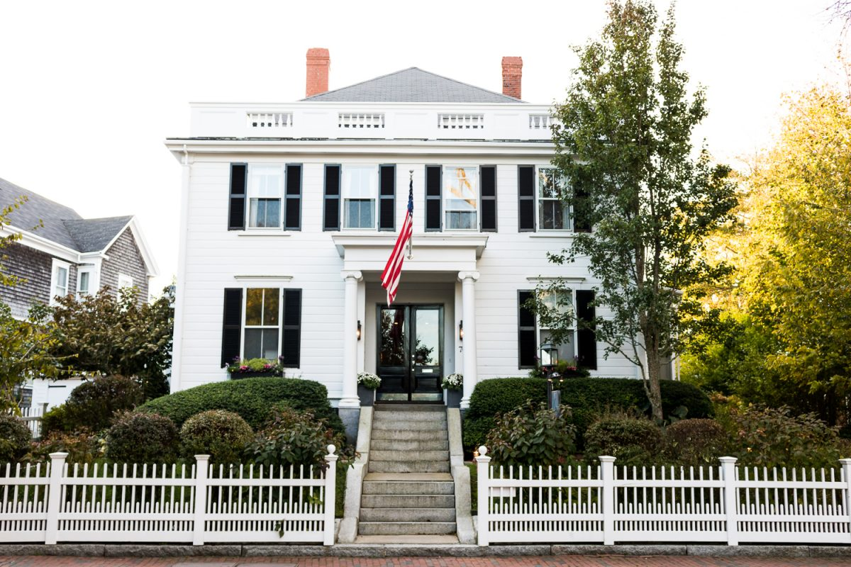 Black shutters on a white colonial style house which is a hotel in Nantucket, featuring an American Flag over entryway and white picket fence in front of the home