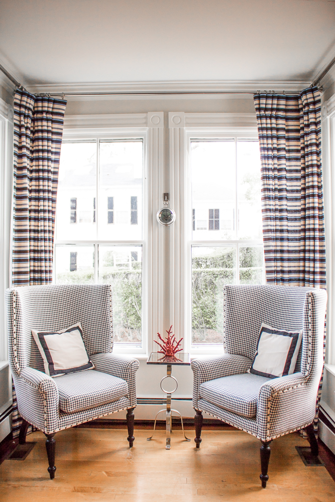 Houndstooth patterned sitting chairs with white and black pillows in corner of a room in front of two large windows