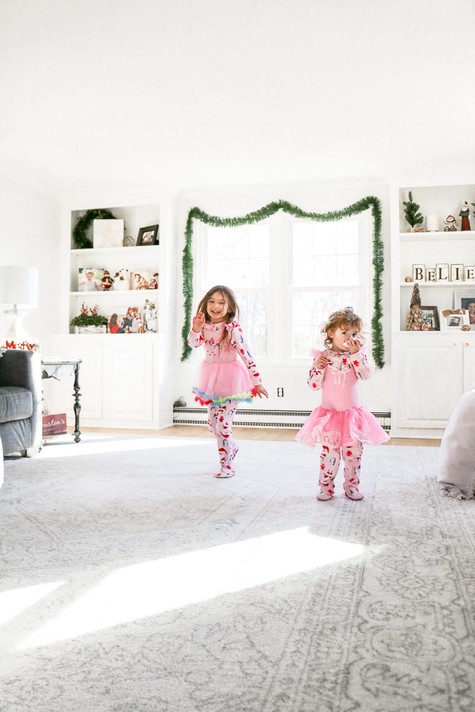 Little girls wearing pink pajamas and pink tutus dancing and laughing in the middle of a large very white and bright family room decorated for Christmas
