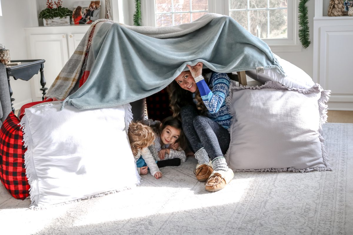 Blanket and Pillow Fort with Woman in blue shirt and children peeking out  from inside