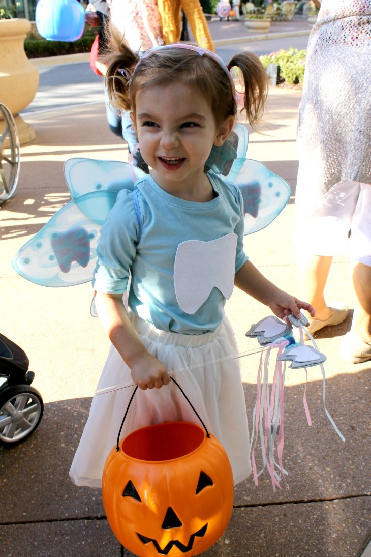 Toddler wearing a blue shirt wth a white tooth on it and a white tutu skirt for Halloween, dressed as a Tooth Fairy