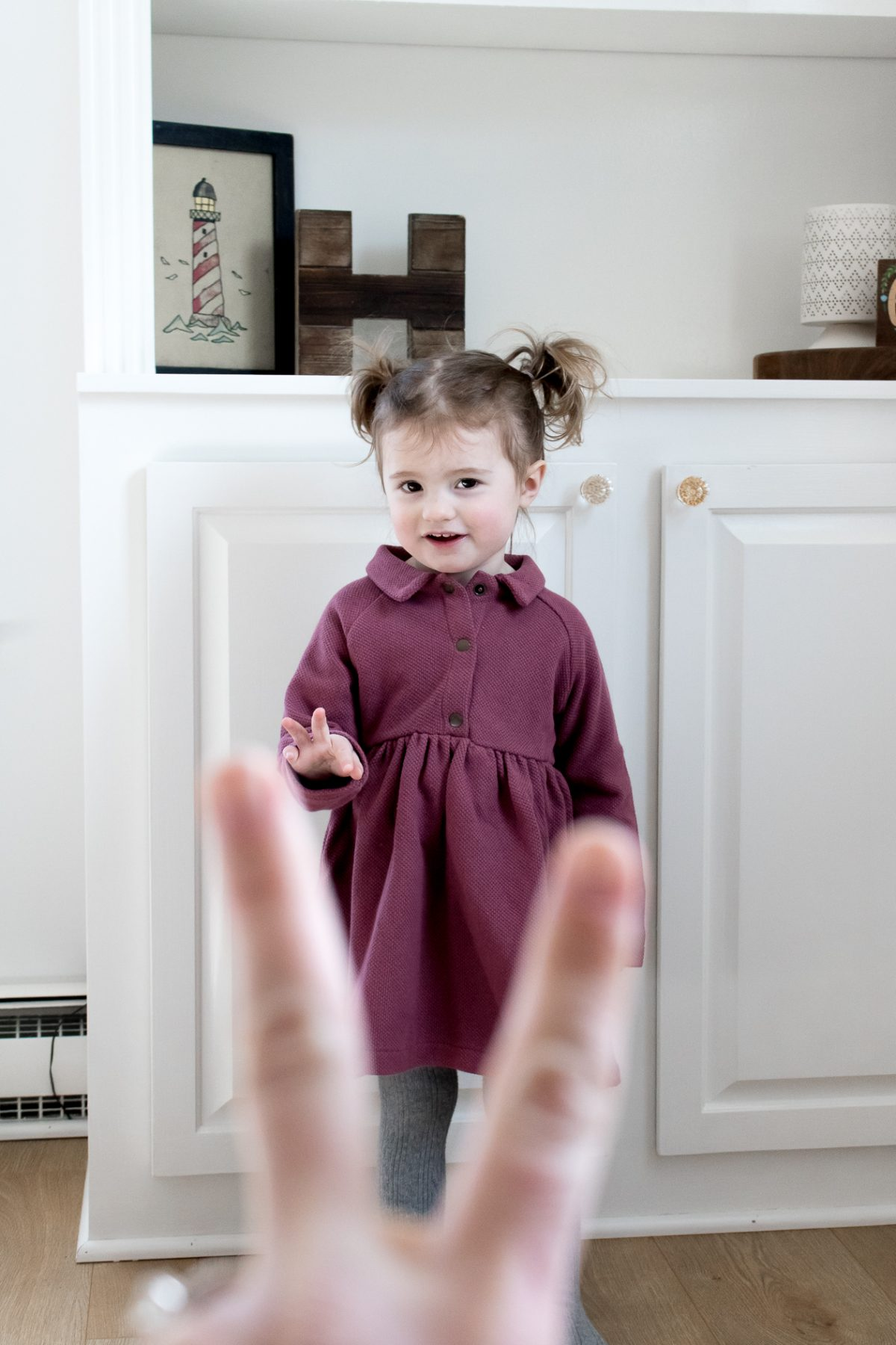 Little Girl with Pigtails in Purple Dress Trying to Hold up two fingers
