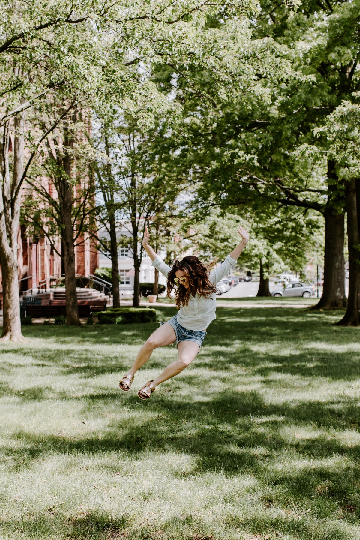 Woman leaping in the air clicking feet together wearing button up shirt and sunglasses and gold sandals