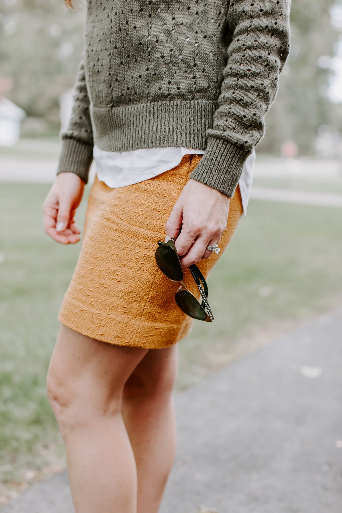 Detail shot of woman holding sunglasses while wearing green sweater and mustard skirt