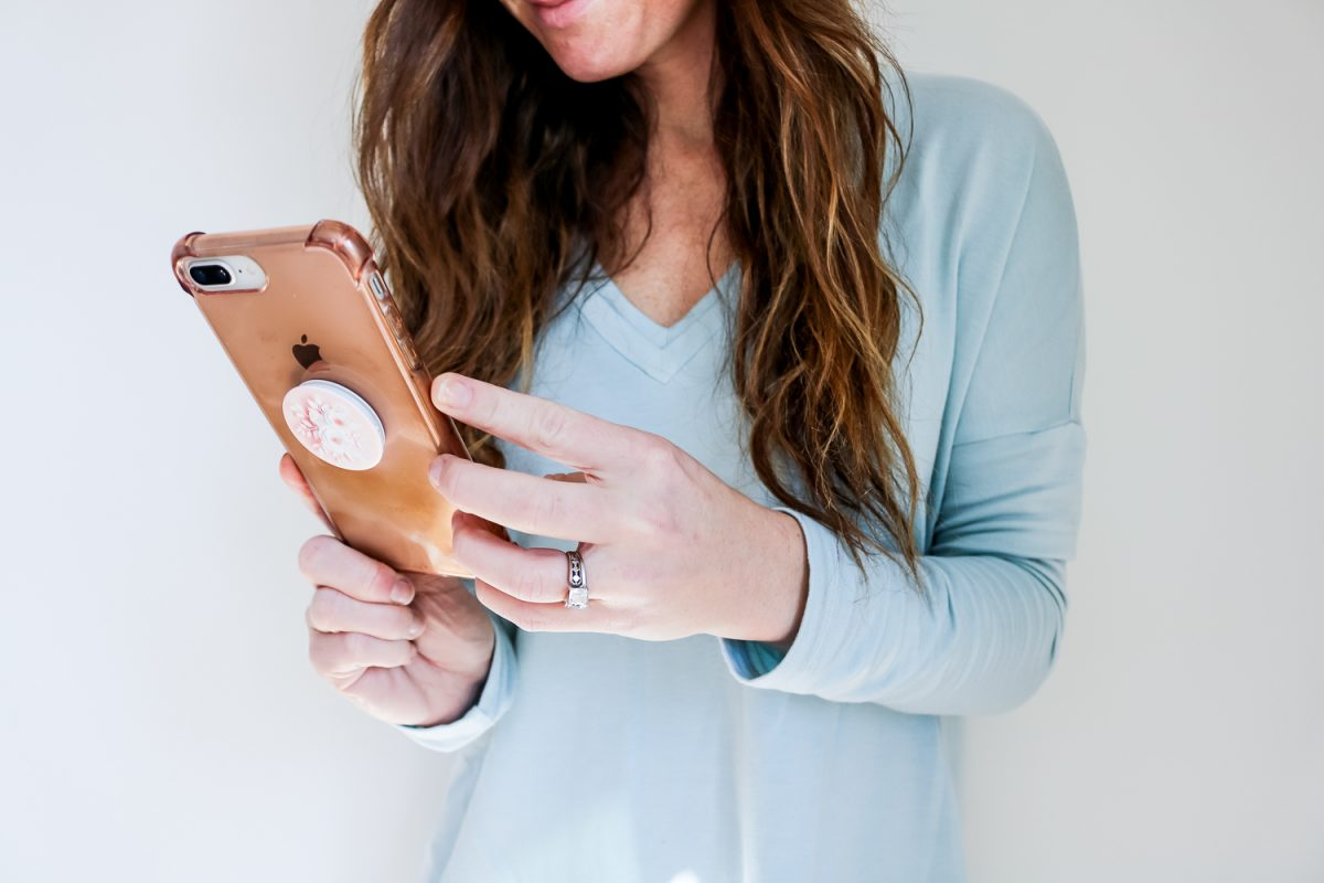 Growing on Instagram secrets - woman wearing blue shirt wearing pink cell phone