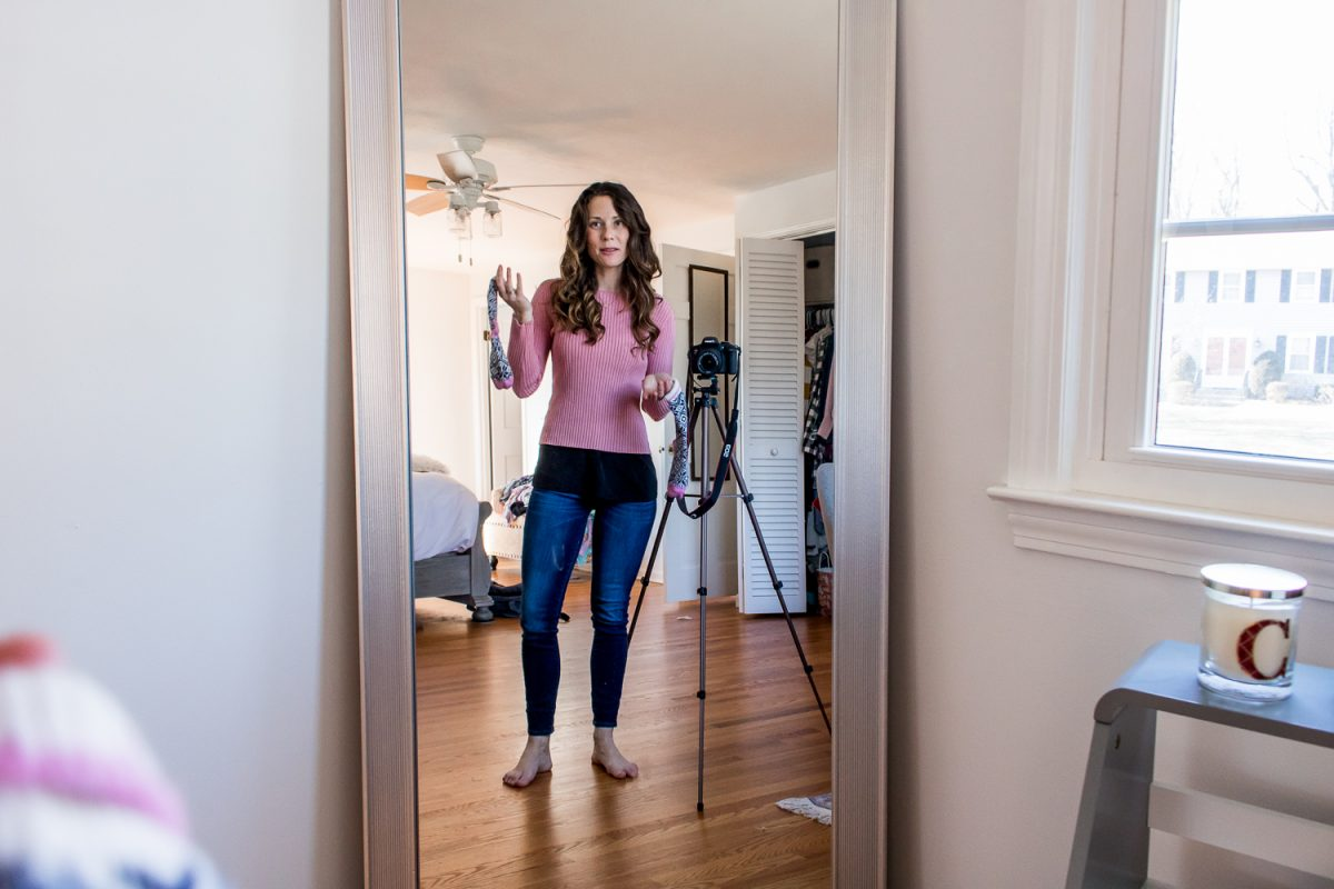 Mom Brain - Woman wearing pink shirt, holding socks, in front of mirror next to camera tripod - Six Crazy Things That Happened to My Body After Pregnancy