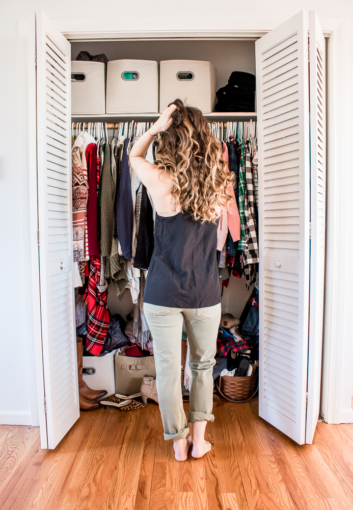 Woman with her hand in her hair wearing a black tank top and green pants standing in front of a messy closet - Six Crazy Things That Happened to My Body After Pregnancy