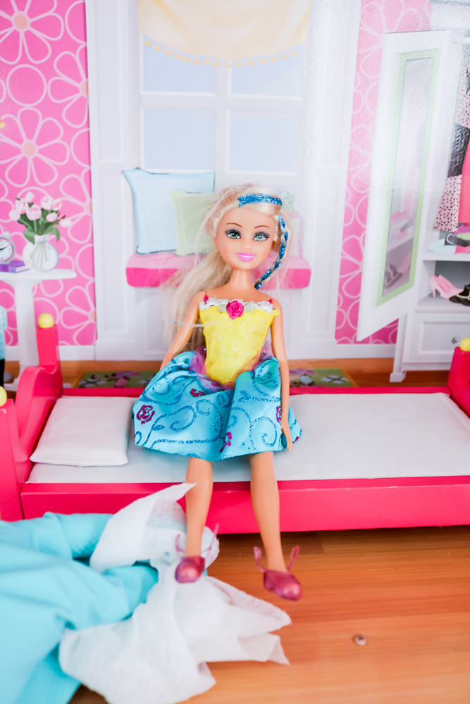 Blue Gloved Hand Cleaning Doll Wearing Shoes with a Disinfecting Wipe