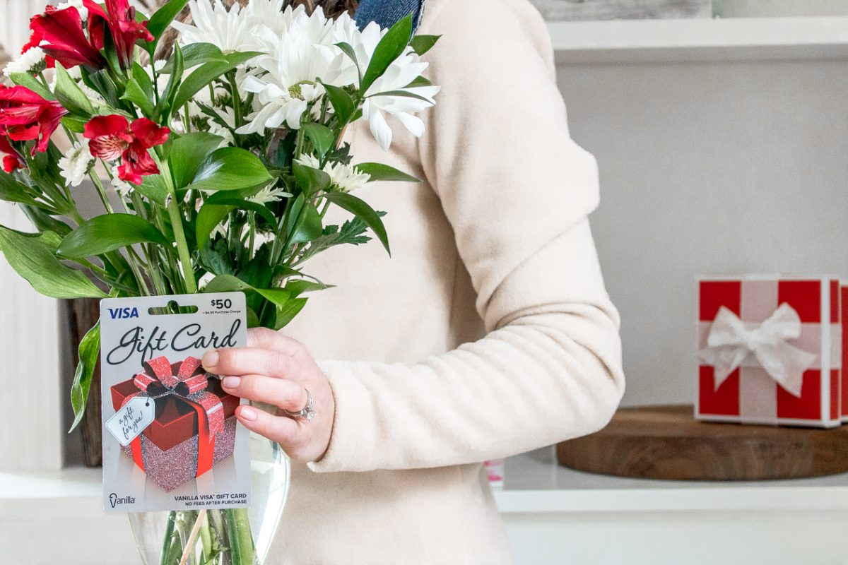 Woman holding a $50 gift card and a bouquet of flowers - Last Minute Valentine's Day Gifts