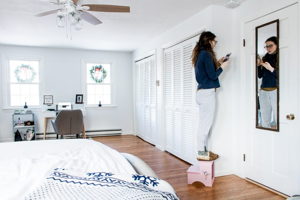 Woman Installing Fire Alarm on Ceiling in Bedroom - How to Keep Your Family Safe with Onelink Smart Smoke & Carbon Monoxide Alarm