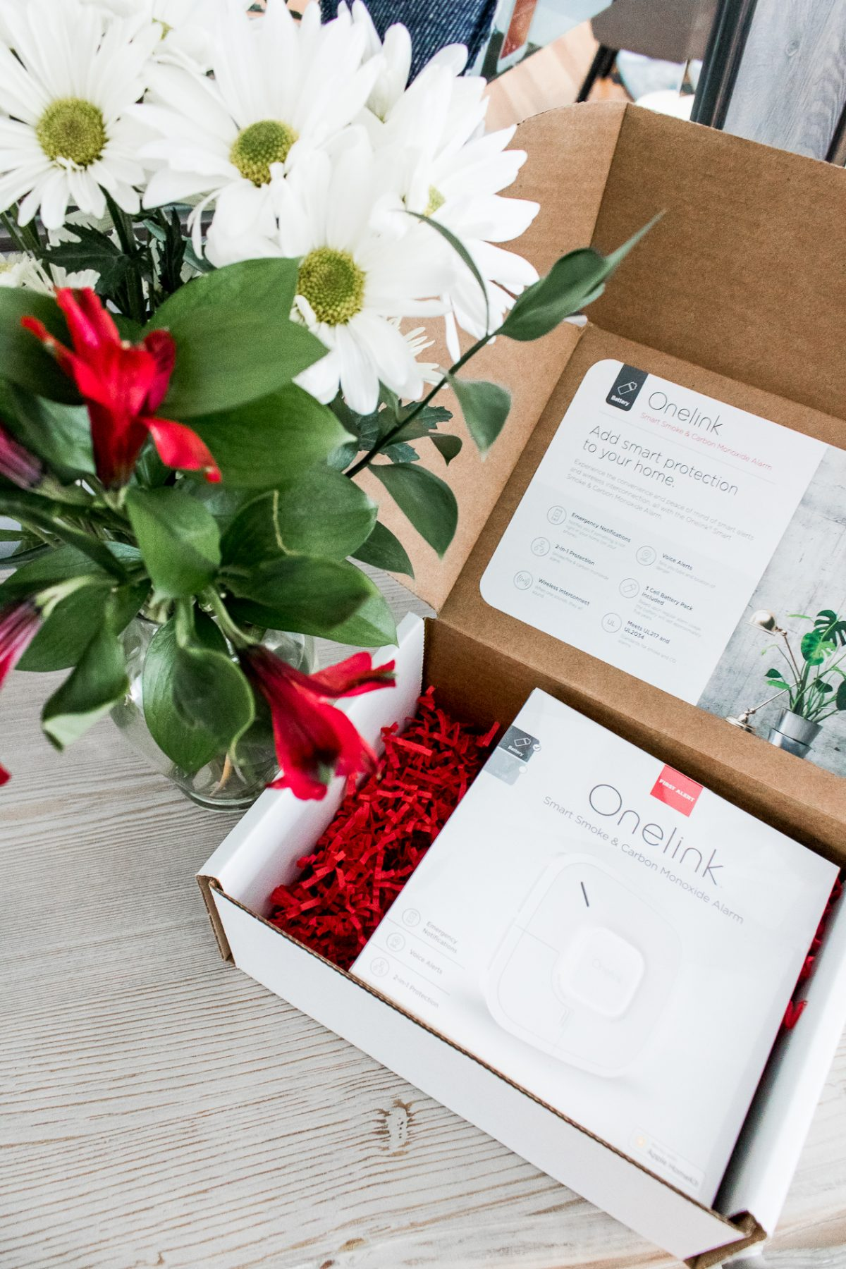 Overhead photo of Flowers and Onelink Smart Smoke & Carbon Monoxide Alarm in Box - How to Keep Your Family Safe with Onelink Smart Smoke & Carbon Monoxide Alarm