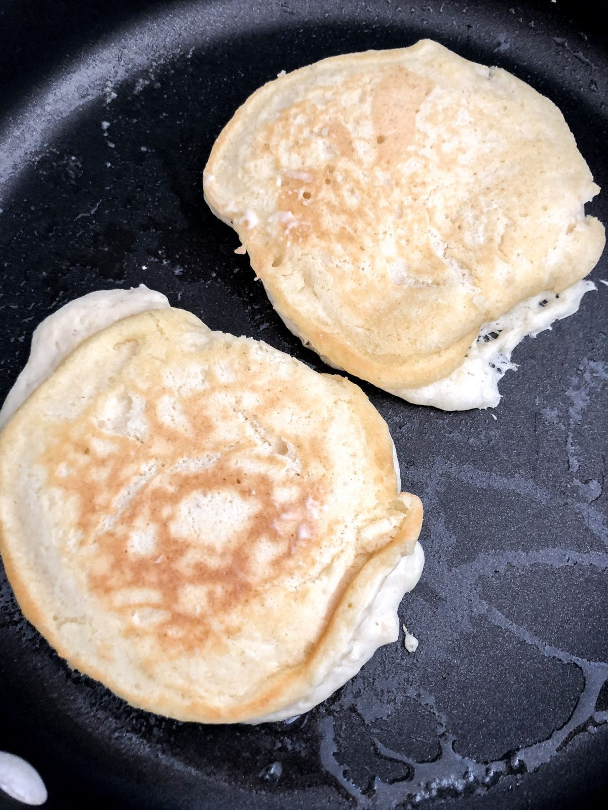Pancakes on a buttered Skillet cooking