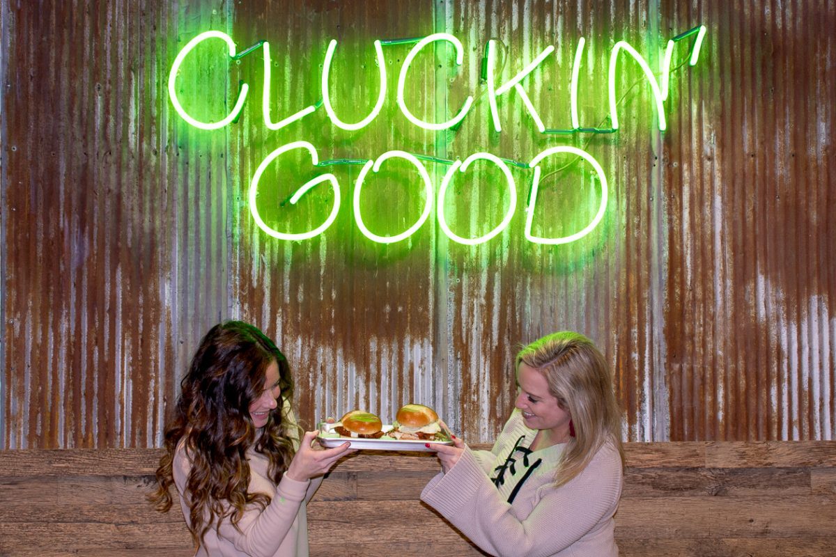 """Two girls in tan shirts holding a tray of chicken sandwiches under a neon sign that says """"Cluckin' Good"""""""