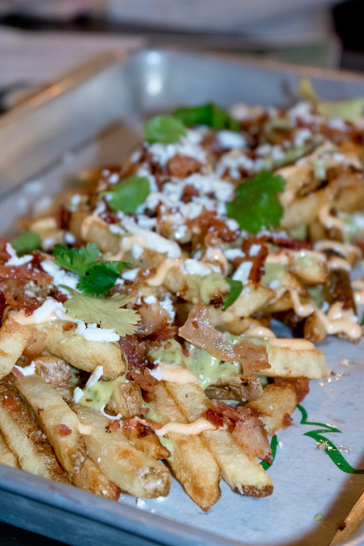 STREET FRIES - Hand Cuts, Tomatillo Guac, Chipotle Aioli, Bacon, Cotija, Cilantro at Roost in Hamden CT
