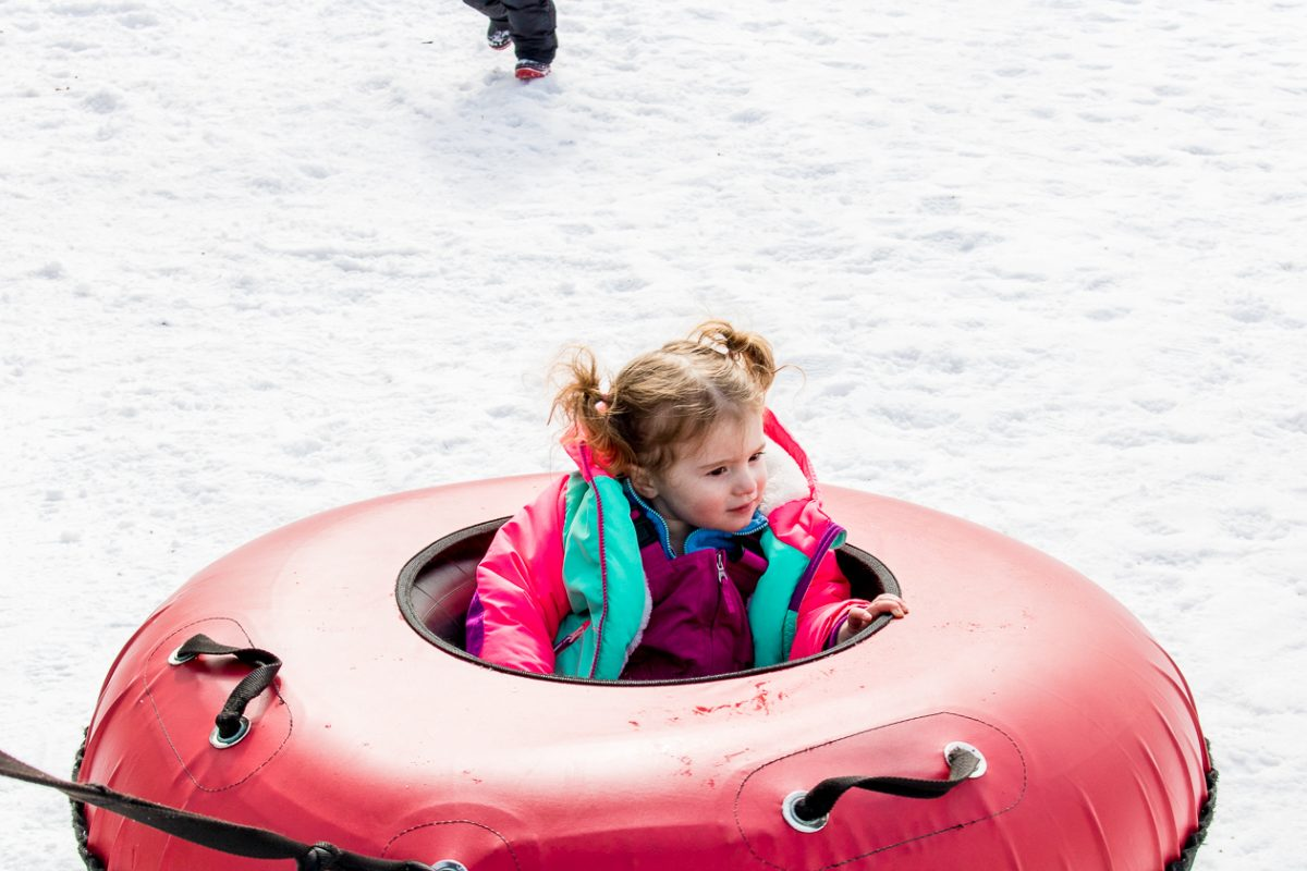 Little girl in pink snow tube at Woodloch Pines Resort in Pocono Mountains