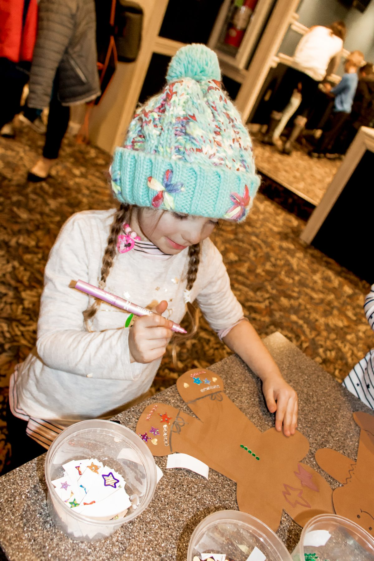 Little girl wearing tan sweater and blue winter hat smiling while making a gingerbread art projects at Woodloch Pines Resort Winter Festival