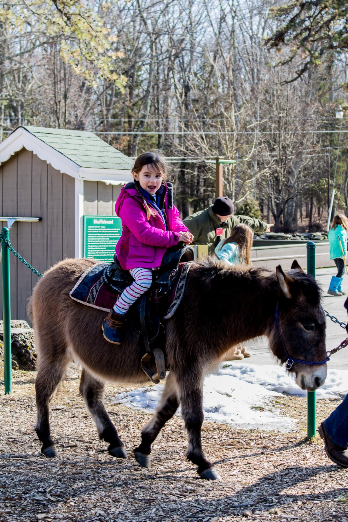 Little girl wearing pink jacket and striped pants riding a pony and smiling at Woodloch Pines Resort