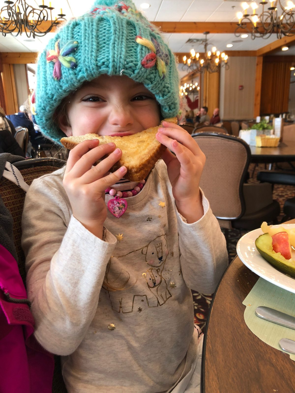 Little girl in blue winter hat eating a grilled cheese at Woodloch Pines Resort in Pocono Mountains
