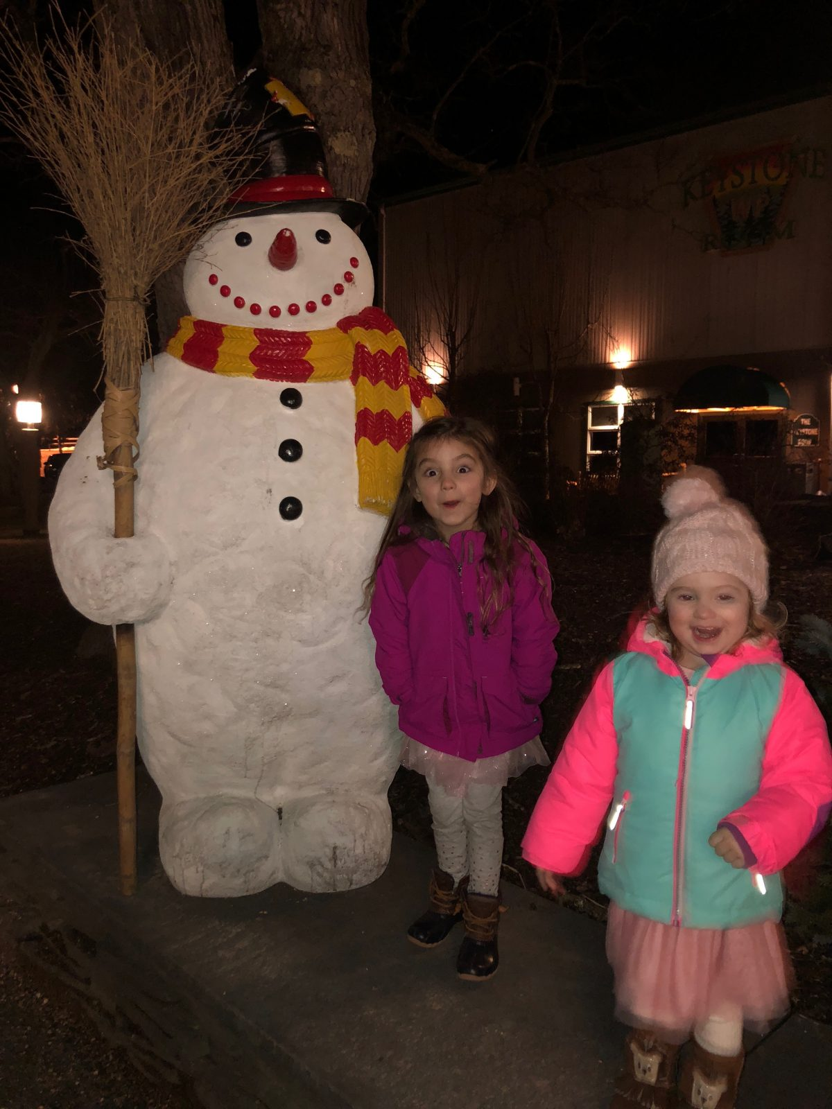 Little girls in winter coats standing by Frosty the Snowman statue at Woodloch Pines Resort in Poconos Mountains PA