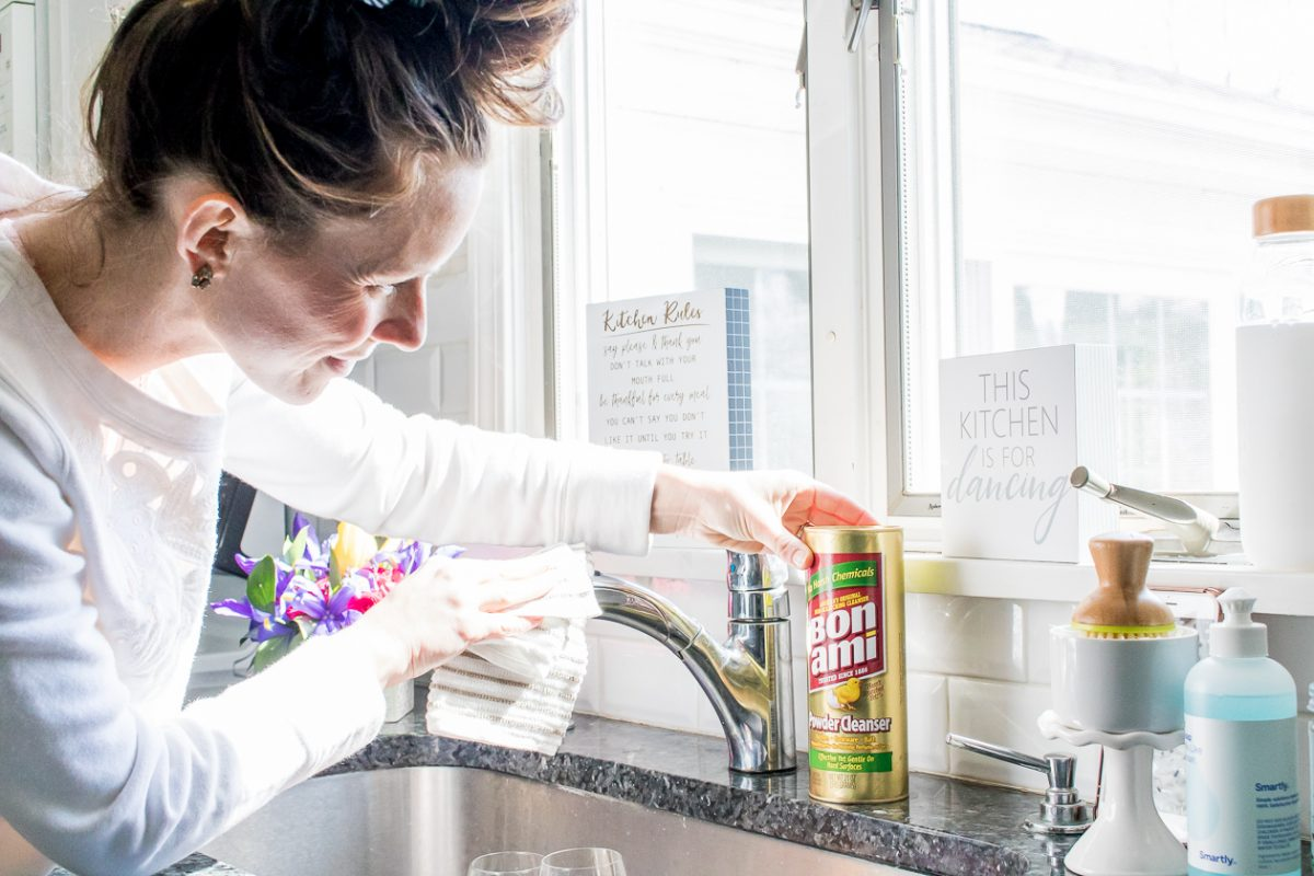 Woman wearing white sweatshirt using Bon Ami Powder Cleanser to clean a sink faucet