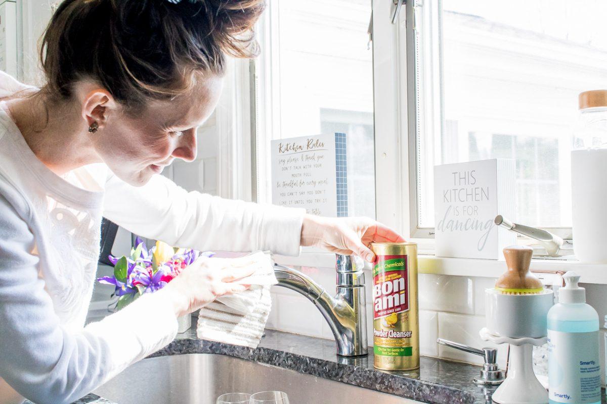 Woman wearing white sweatshirt using Bon Ami Powder Cleanser to clean a sink faucet
