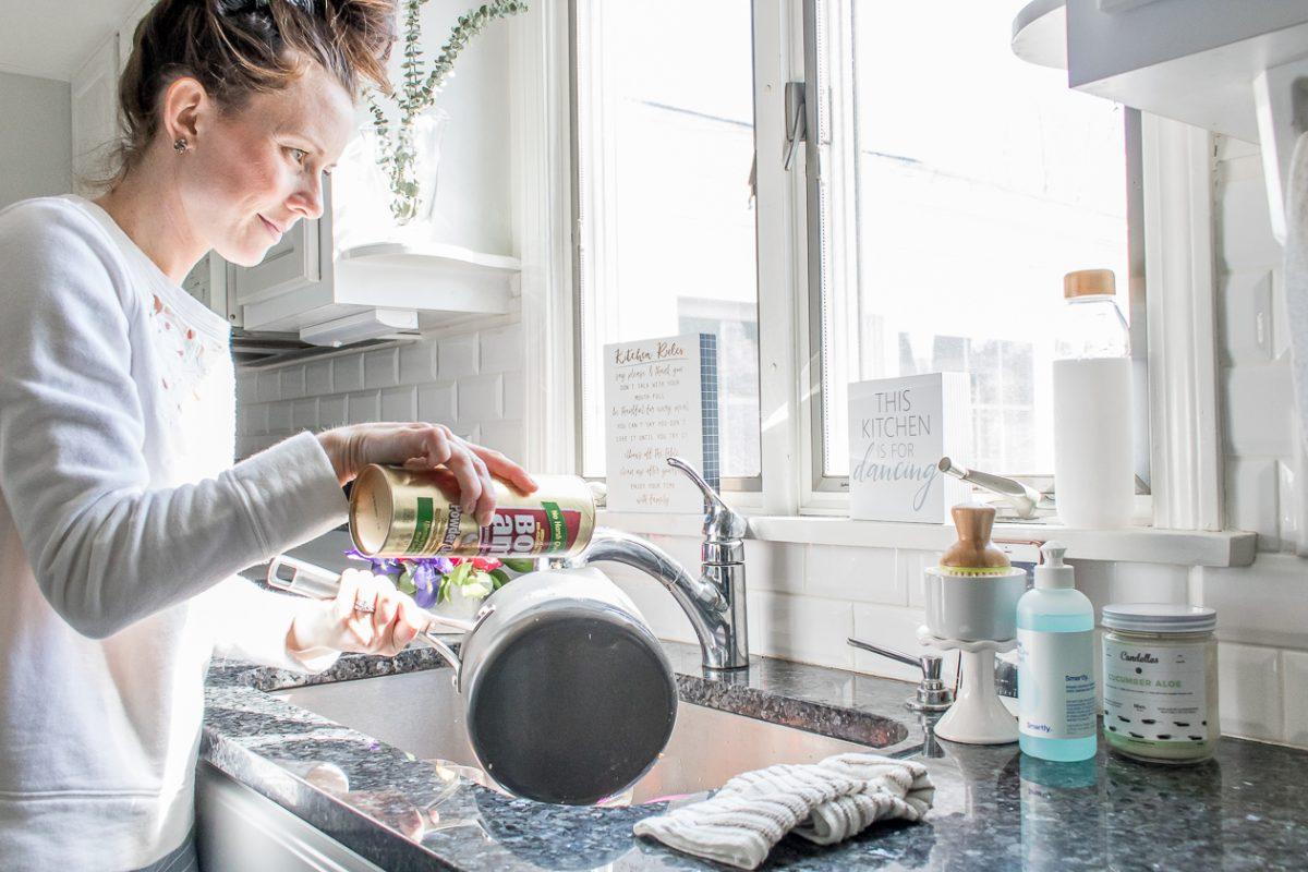 Woman wearing white sweatshirt using Bon Ami Powder Cleanser to clean a pot