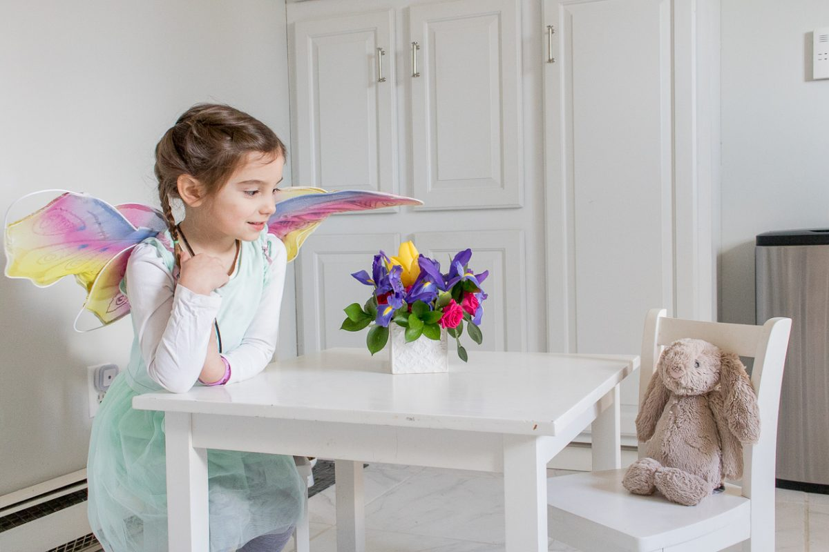 Little Girl wearing fairy wings sitting at a kitchen table for kids with her bunny and a bouquet of flowers