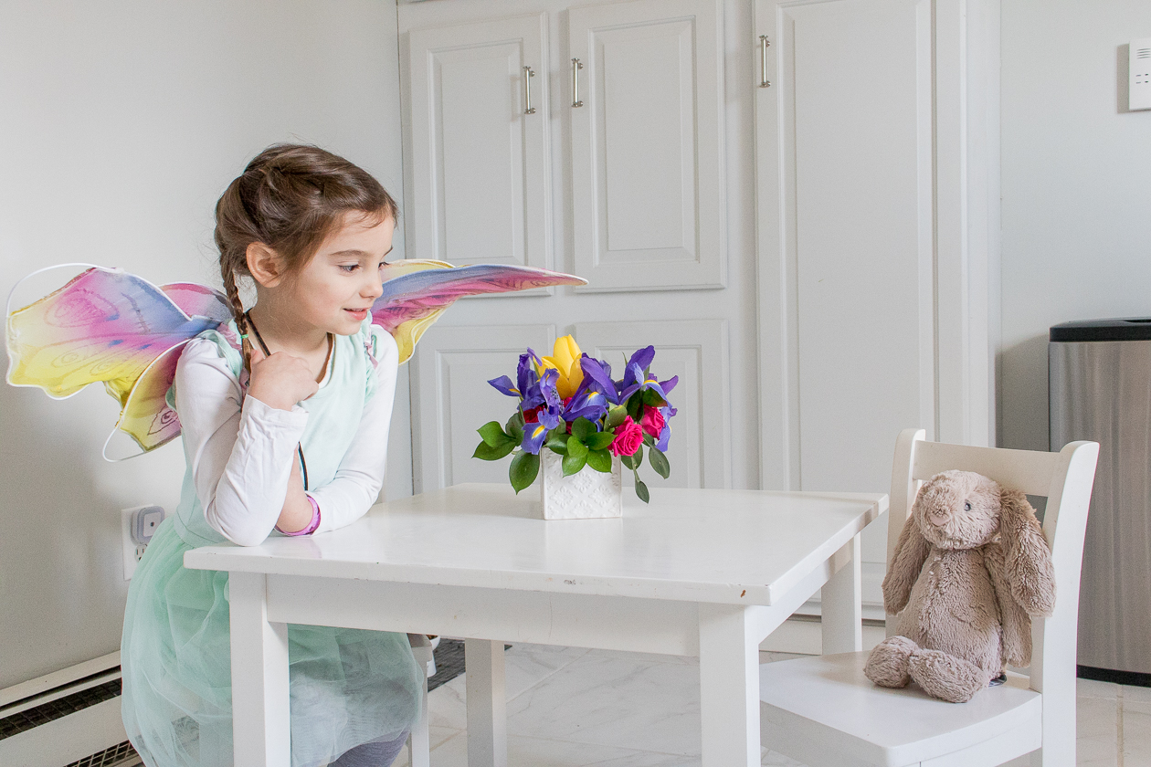 little girl sitting at a white table with fresh flowers and bunny