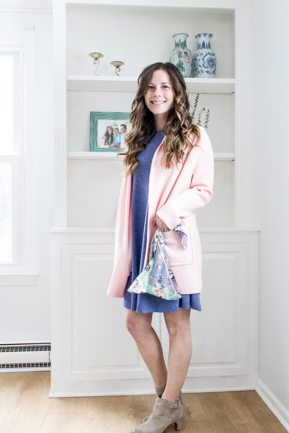 Smiling woman in pink sweater and blue dress