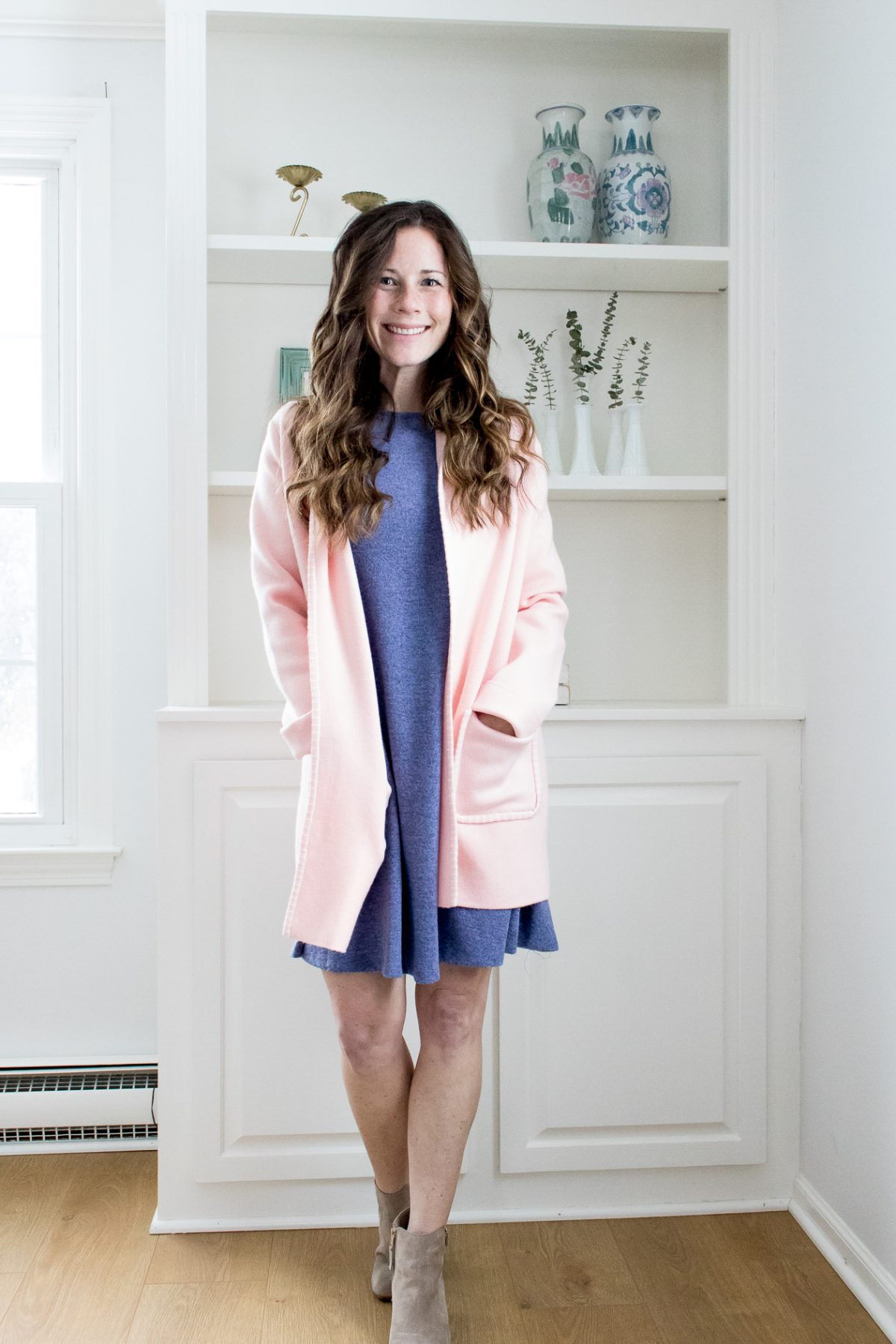 Smiling woman in pink sweater over blue dress