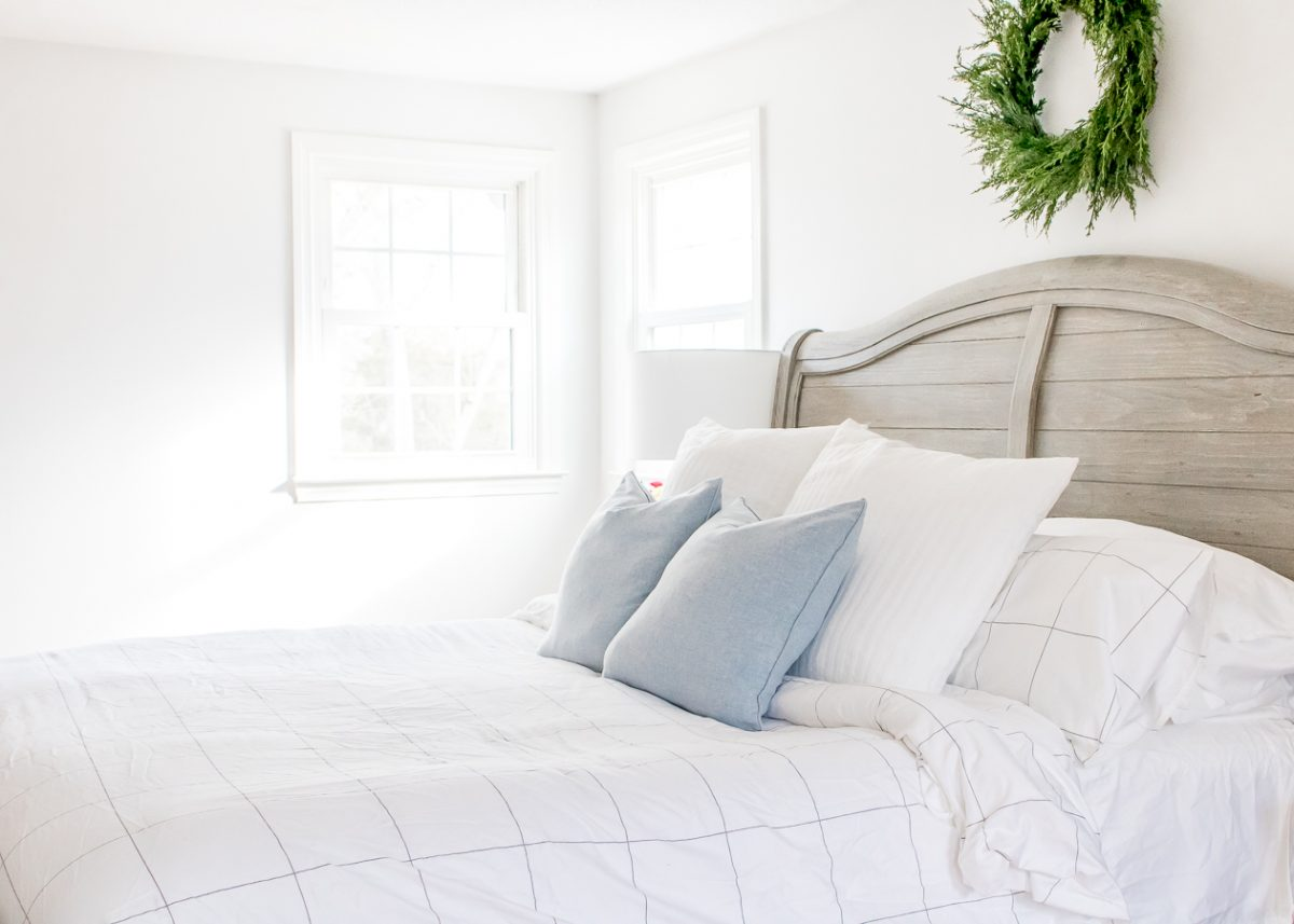 Bright White Bedroom with Gray Headboard and Green Boxwood Wreath on the Wall above the Bed