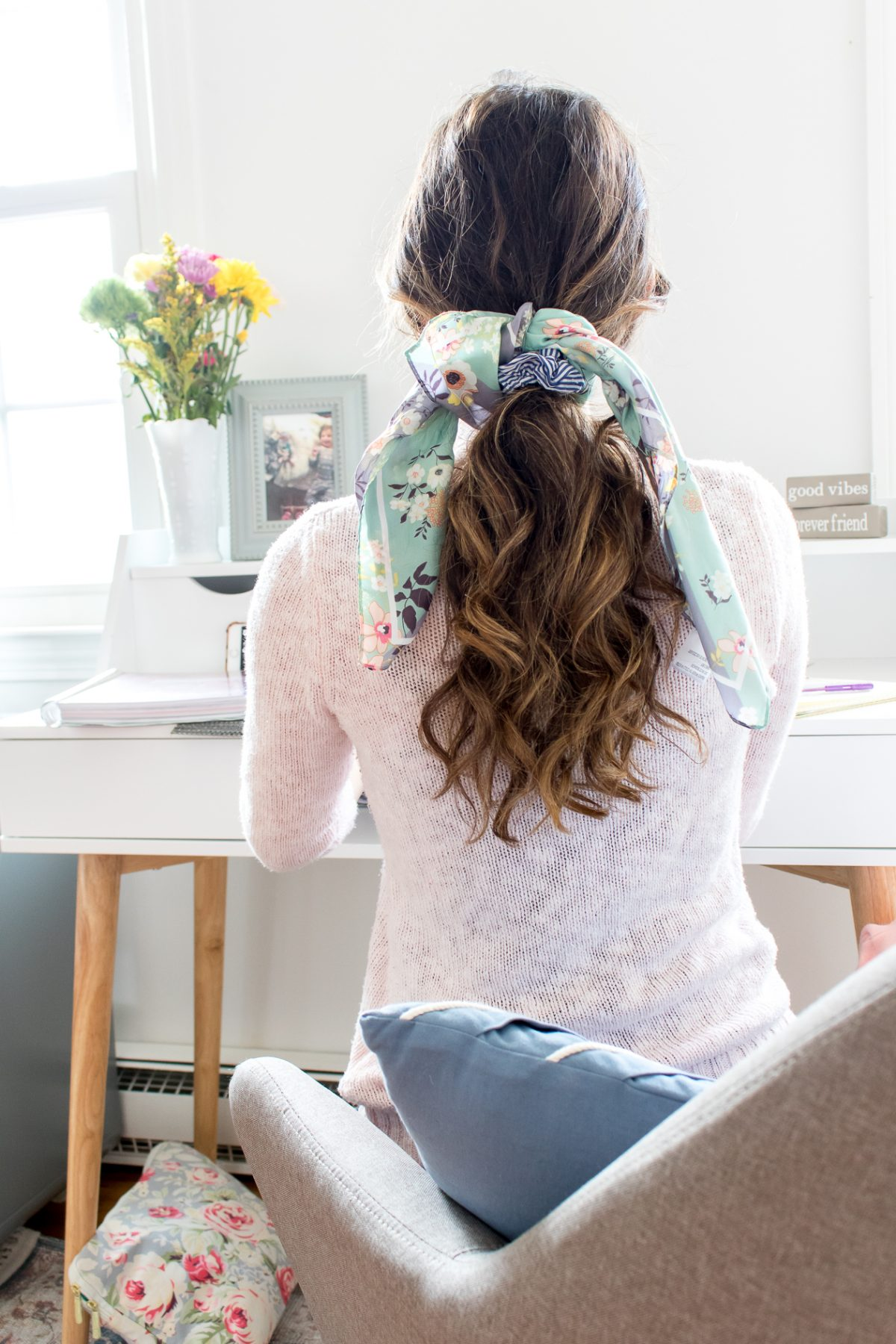 Woman with hair scarf tied around curly pony tail sitting at computer in a pink sweater