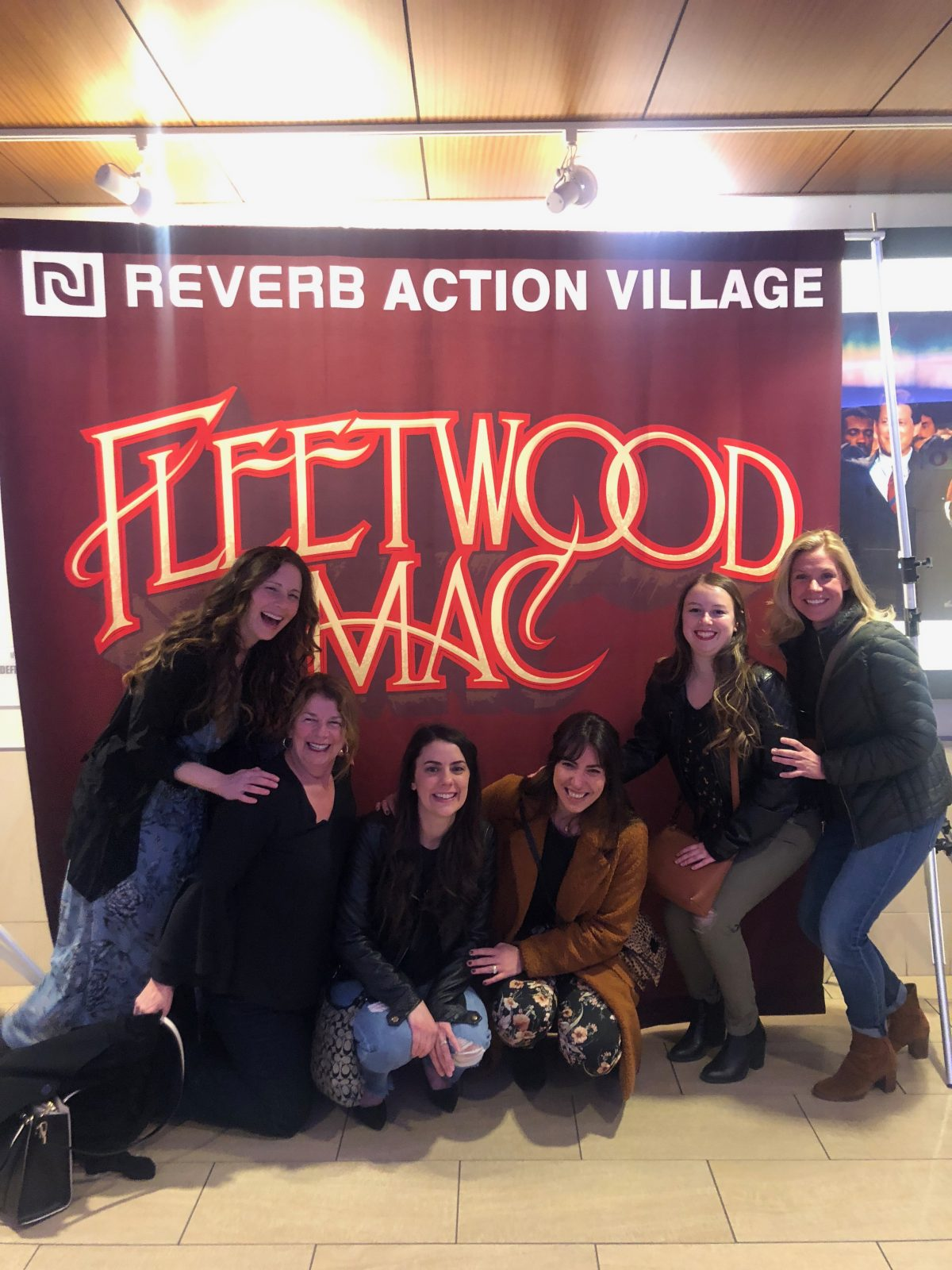 Women posing and laughing in front of Fleetwood Mac sign