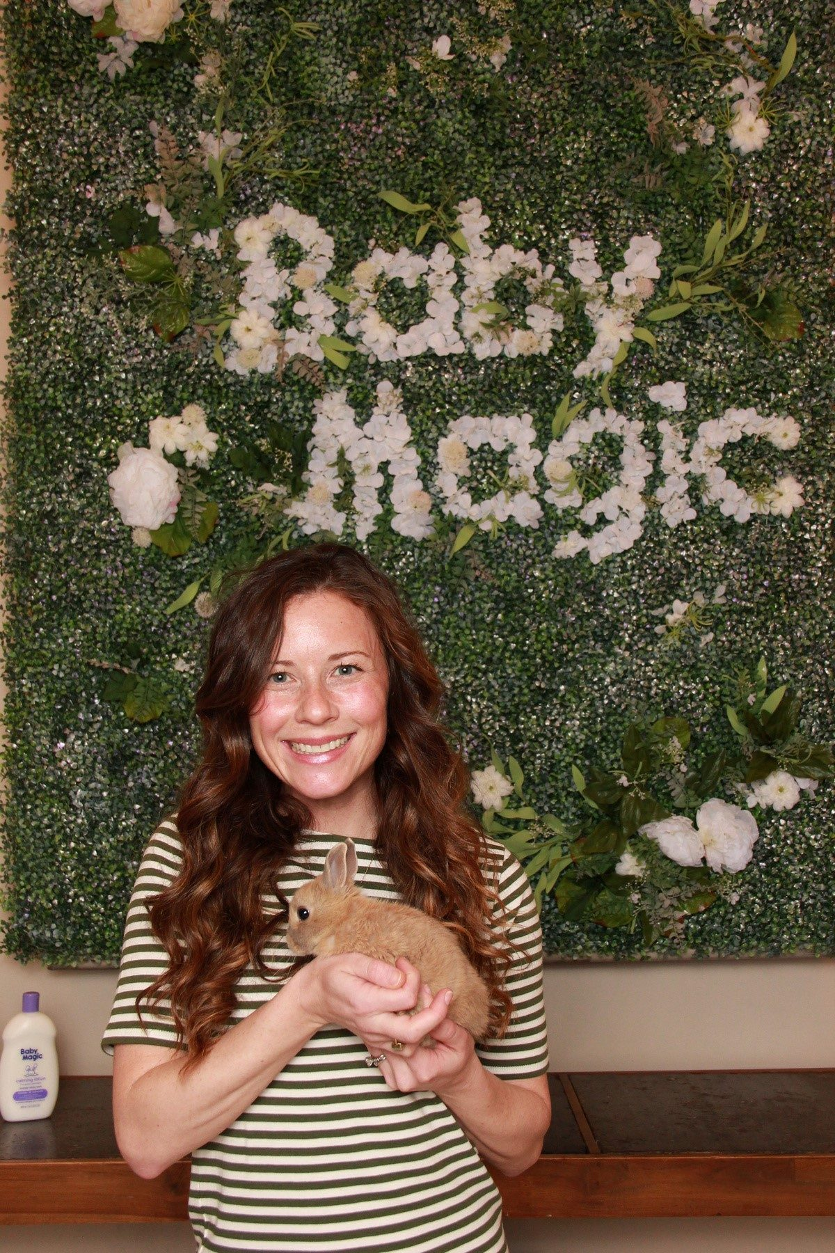 Baby Magic Event Woman wearing green striped shirt holding a baby bunny