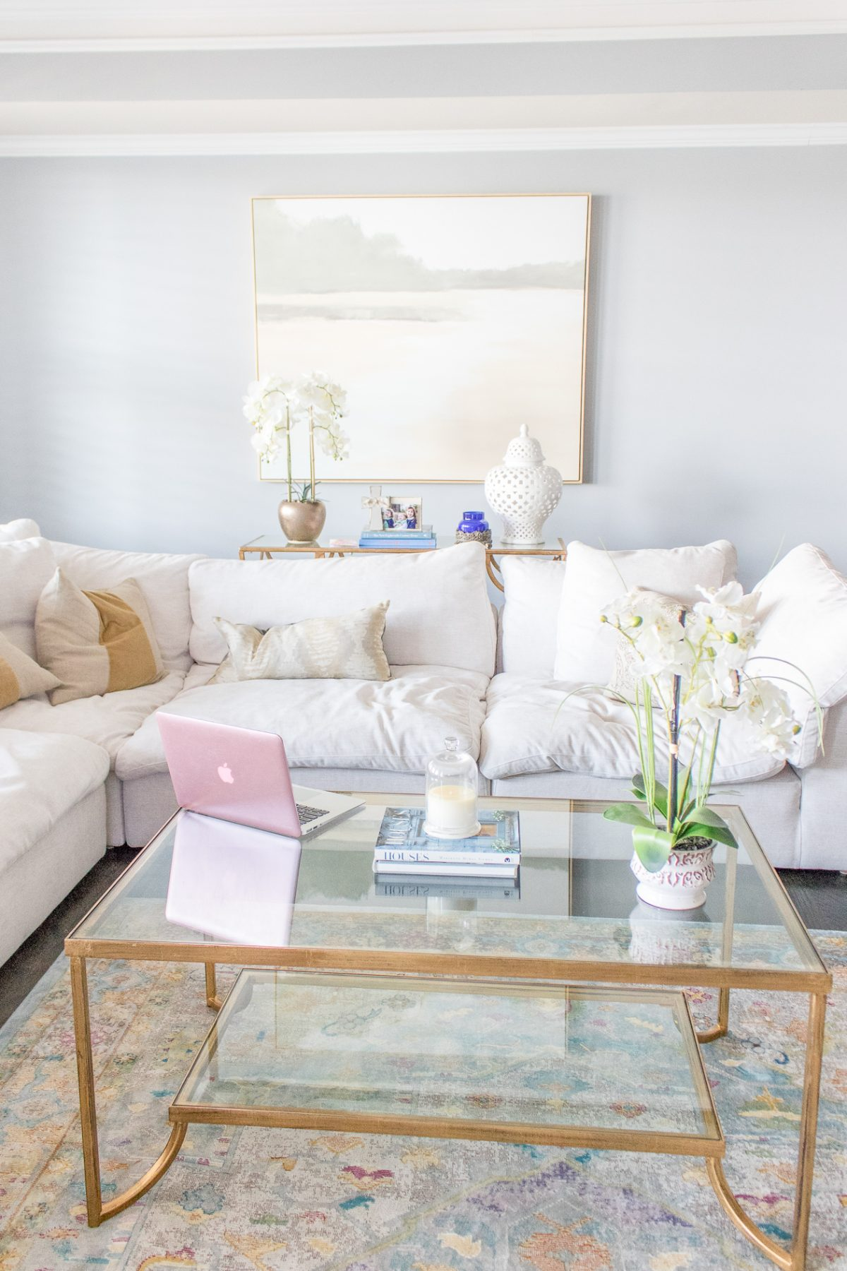 Gray living room with large white couch, glass coffee table, pink Macbook Air, fresh white orchids