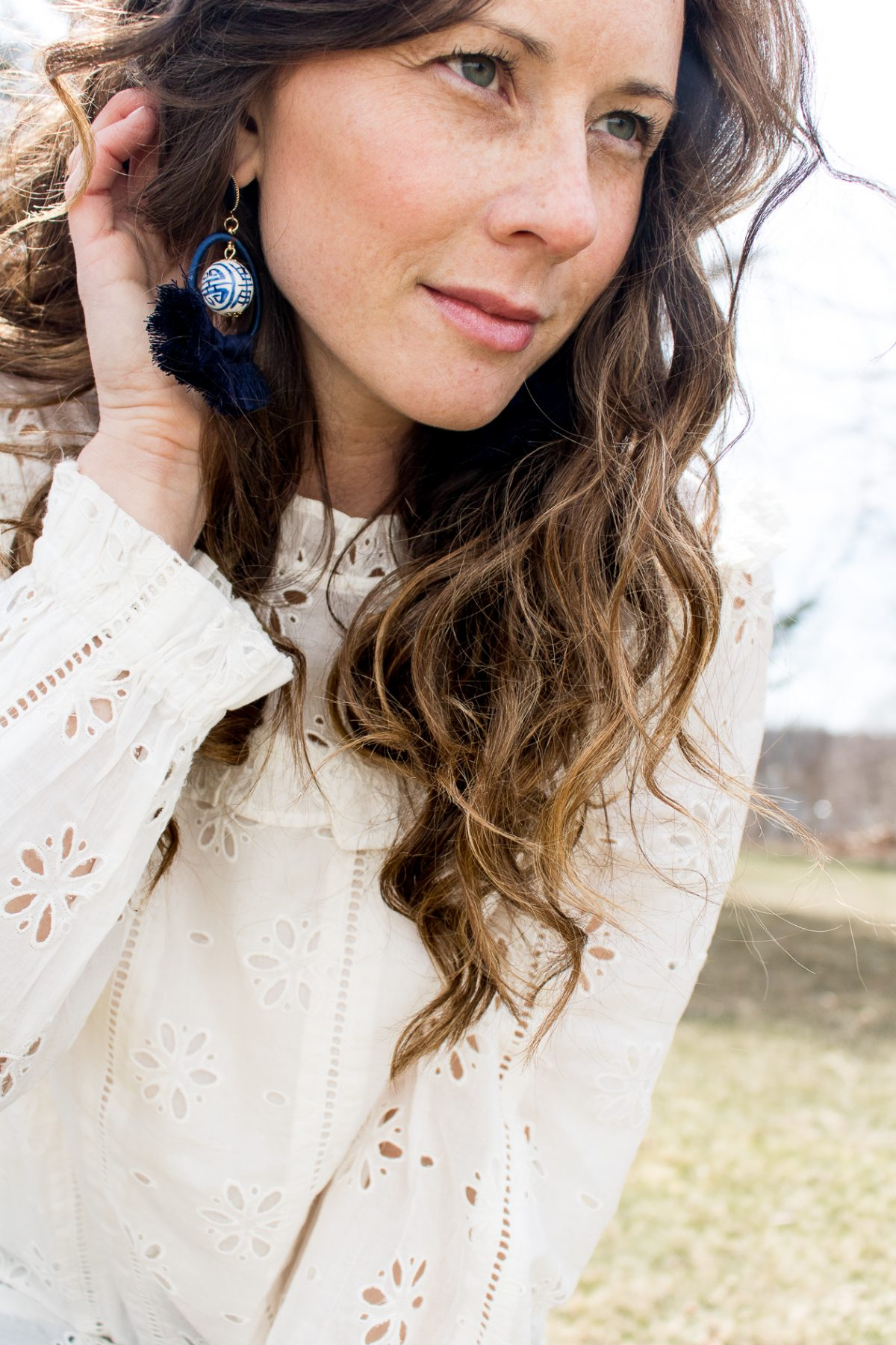 Close Up on a Woman with her hand behind her ear to show her blue and white chinoiserie tassel earrings
