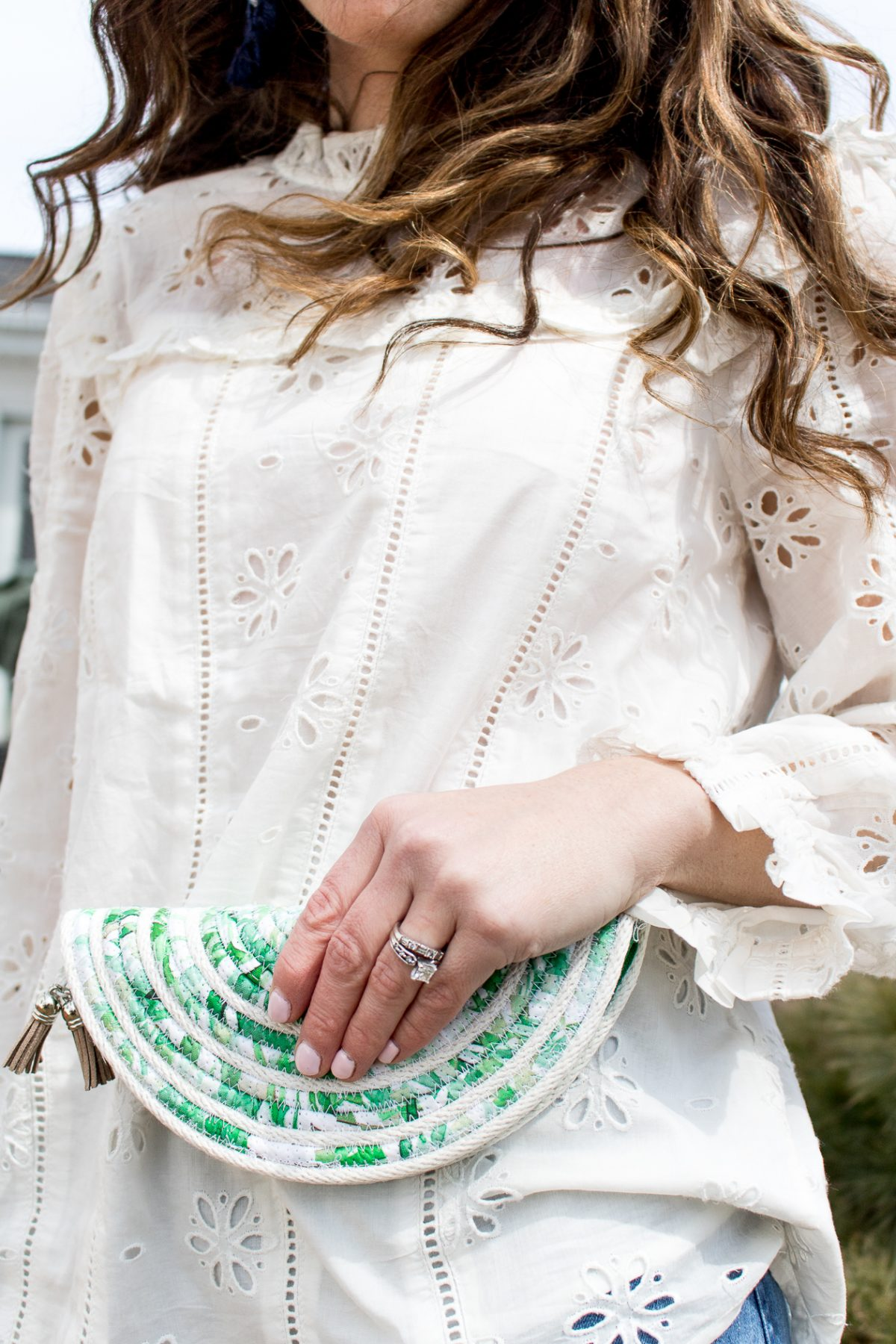 Womans hand with pink nail polish holding green woven purse