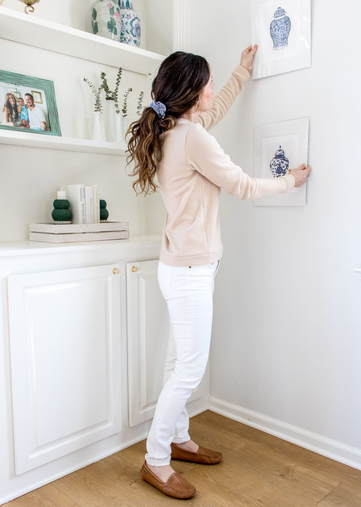 Woman wearing tan Dudley Stephens fleece top, white denim, tan woven loafers with hair pulled into low ponytail, hanging chinoiserie prints on the wall