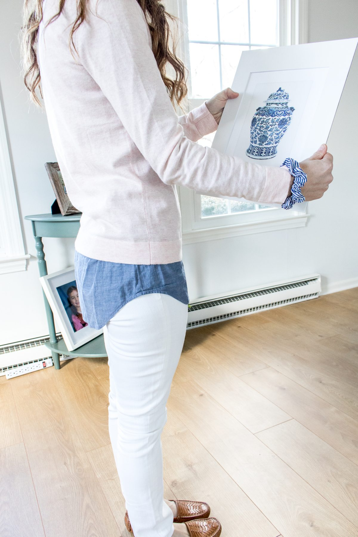 Woman wearing pink Jcrew Sweater over a chambray shirt, white denim, and woven loafers, holding a chinoiserie print