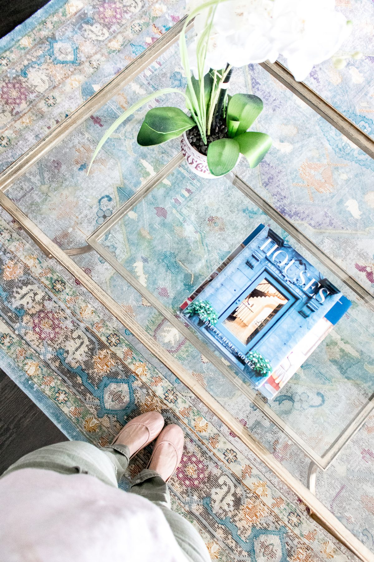 Ariel view of Nantucket Houses Coffee Table Book on Glass Coffee Table and Woman standing beside it wearing pink Tieks, green pants and a pink shirt