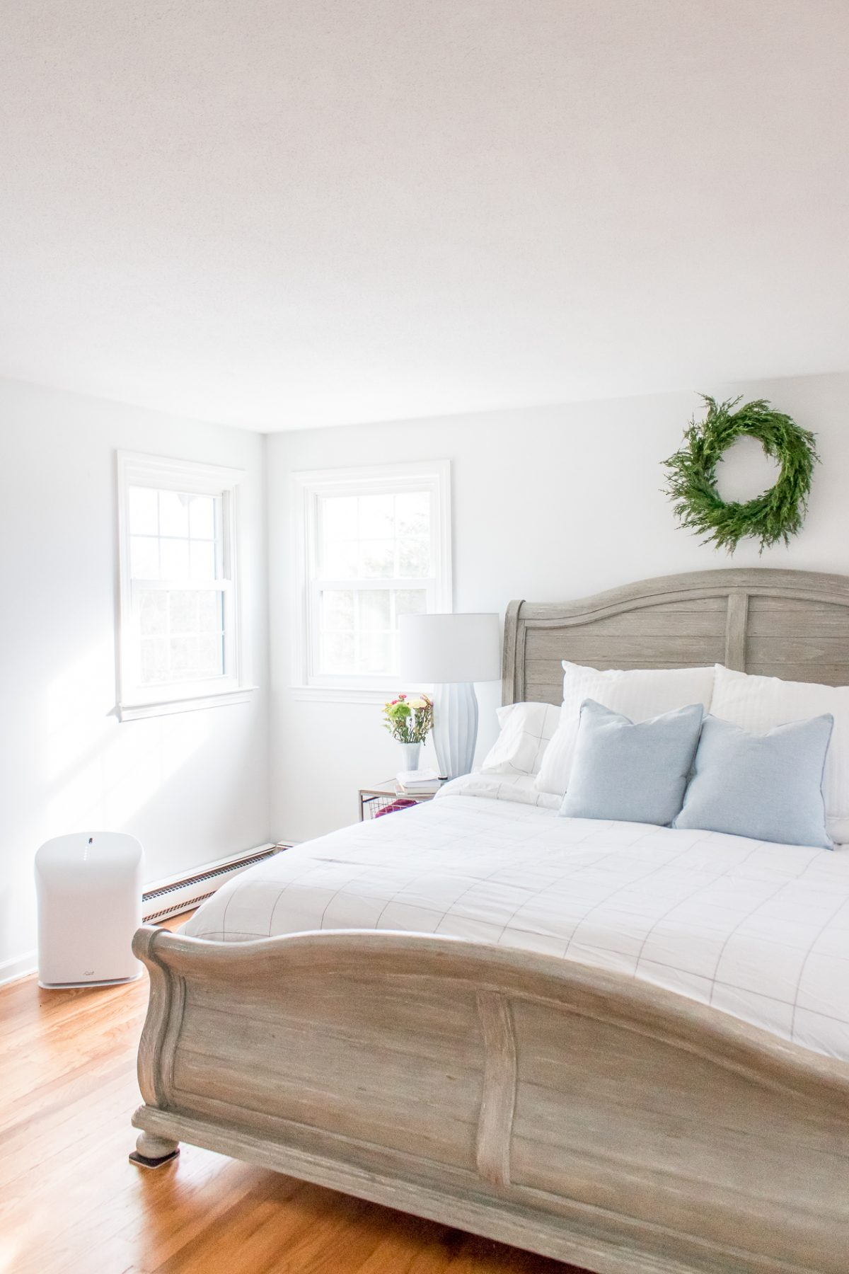 Bright White Bedroom with Gray Headboard and Green Boxwood Wreath on the Wall above the Bed and Rabbit Air Purifier near the wall in the room