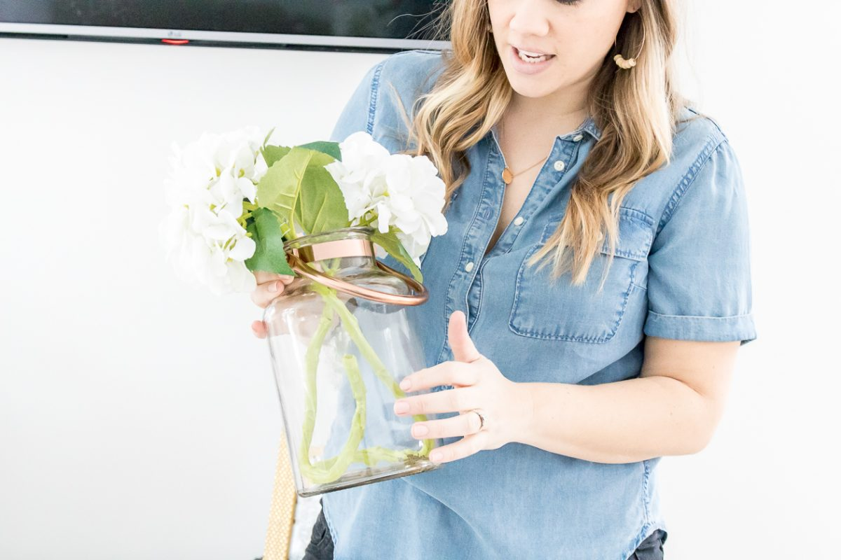 Woman wearing chambray button up shirt holding glass vase with faux flowers