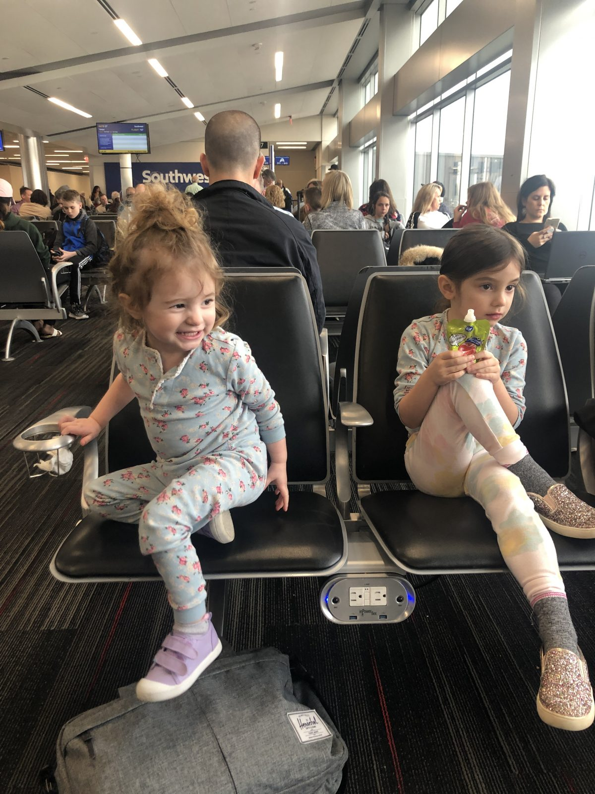 Toddlers waiting to board a plane in seating area