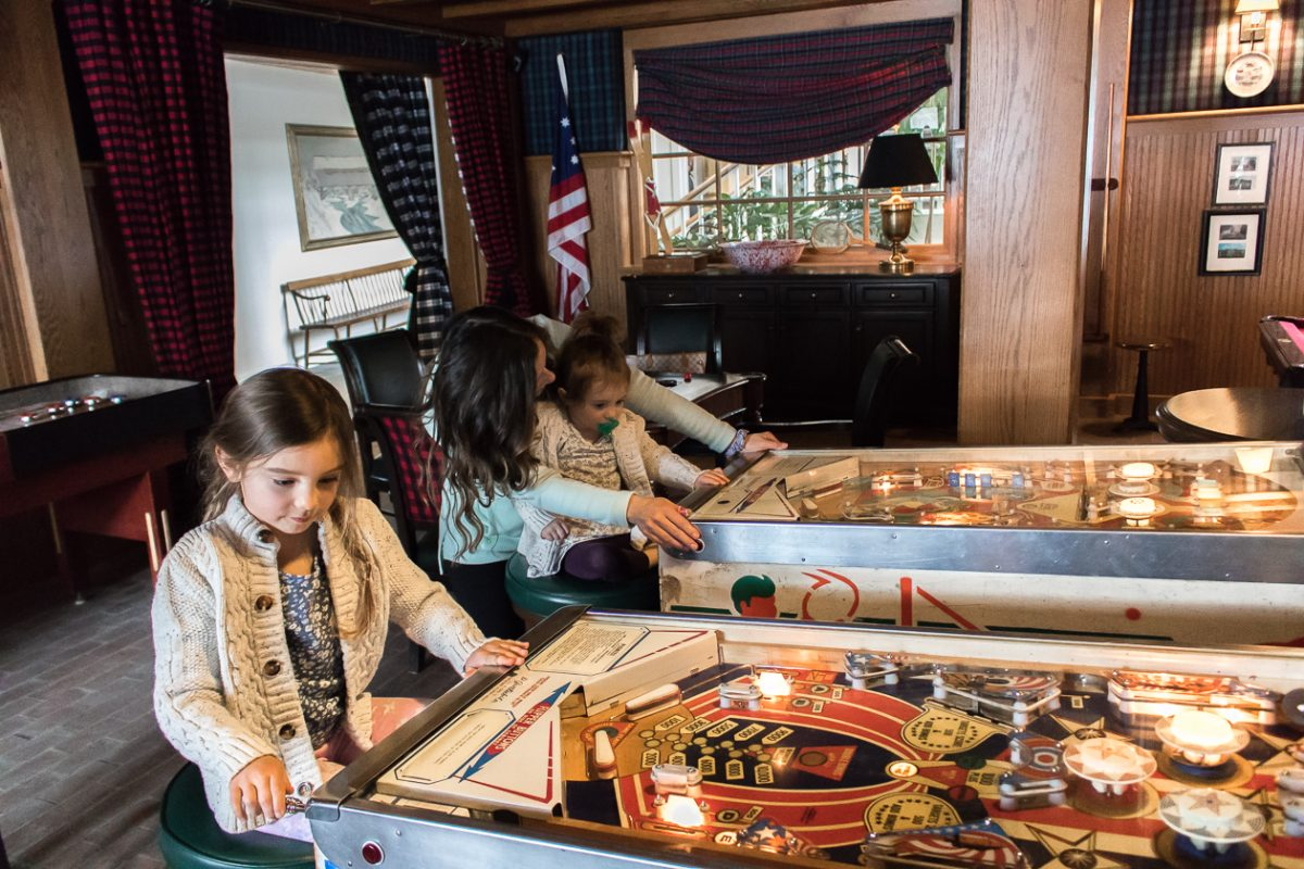 Family playing in the Retro Game Room with old fashioned pinball at Woodstock Inn and Resort in Woodstock Vermont