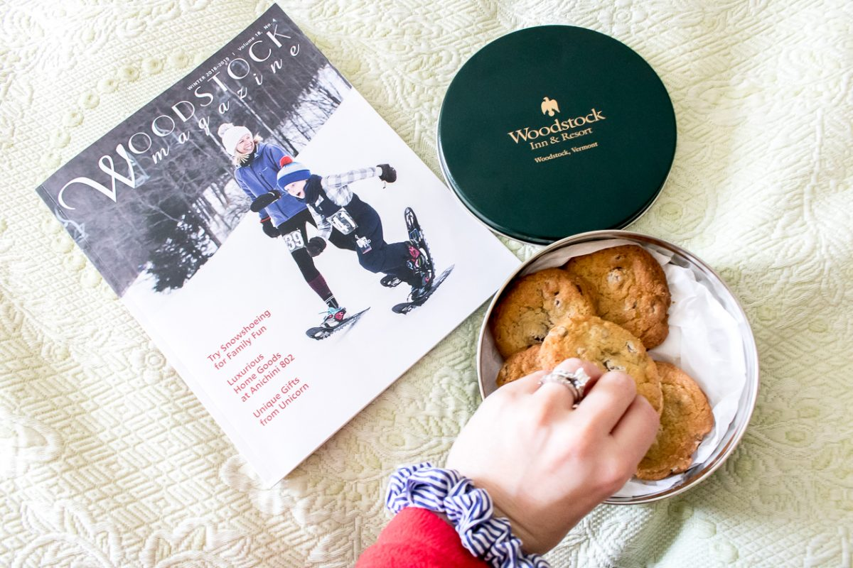 Woodstock Magazine and hand reaching into green tin of chocolate chip cookies